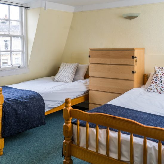 two single beds and on either side of a chest of drawers