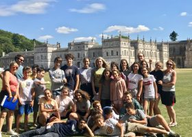 group of summer school students in front of grand building