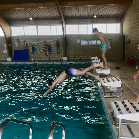 teenage boy diving into an indoor swimming pool