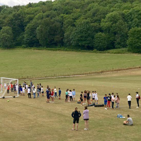 group of school kids standing on a sports field